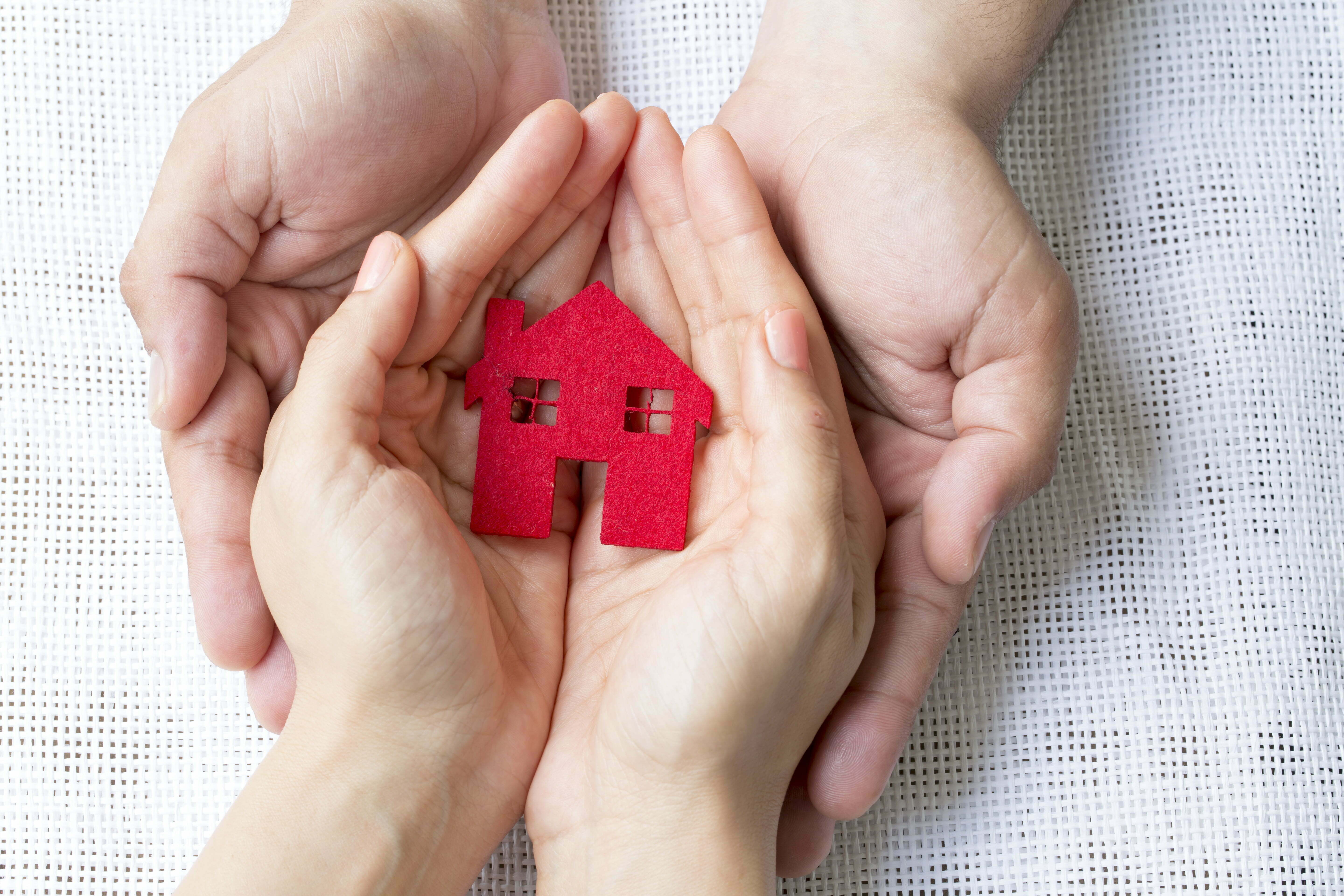 Hands holding a red paper house as a logo for LGBTQ+ housing assistance