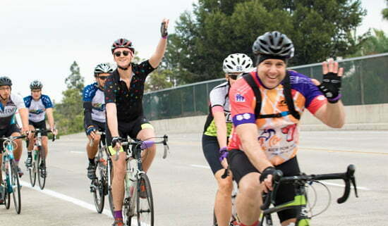 LGBTQ+ cyclists waving as they ride in the Orange County Ride for AIDS event